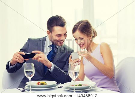 restaurant, couple, technology and holiday concept - smiling woman showing picture to husband or boyfriend on smartphone at restaurant
