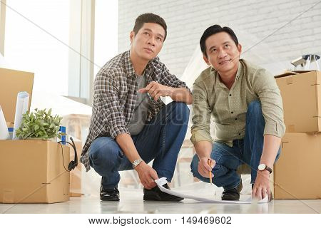 Vietnamese coworkers with blueprint planning design of office