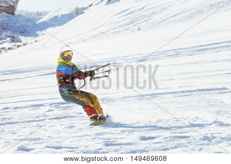 Girl snowboarder rides with snow kite. Snowkiting
