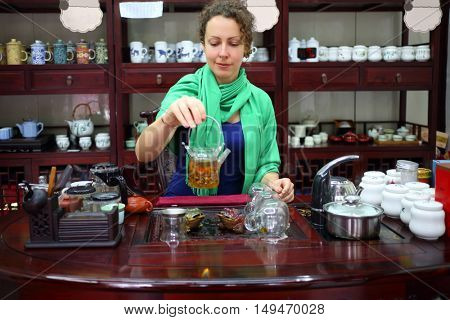 Pretty woman with chinese teapot and cups sits at table in room