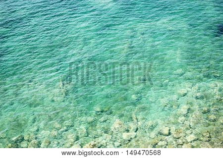Fantastic blue sea background. The azure sea transparent as a tear water