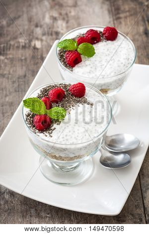 Chia yogurt with raspberries in a glass cup on wooden table