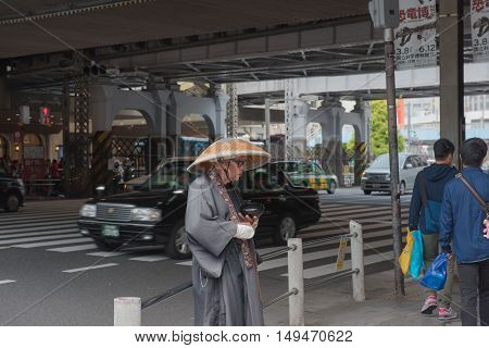 TOKYO  , JAPAN - MAY 2 , 2016:  Buddhist Monk asking for donation from people in  Tokyo Japan. soft focus . Tokyo, Japan. MAY 2 2016.