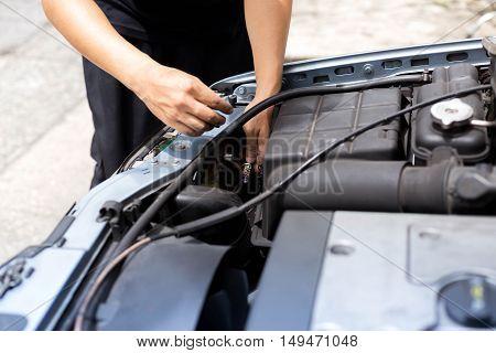 Mechanic changing headlight bulb in a car in garage