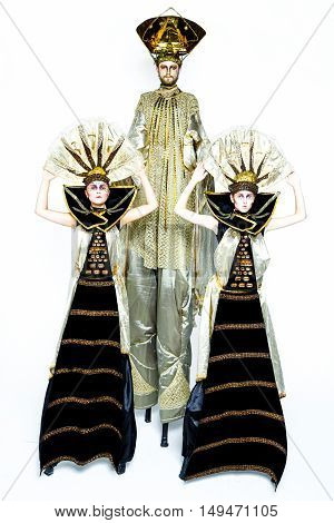 Beautiful Golden Venetian Carnival Masked man and two women on white background, sun costume