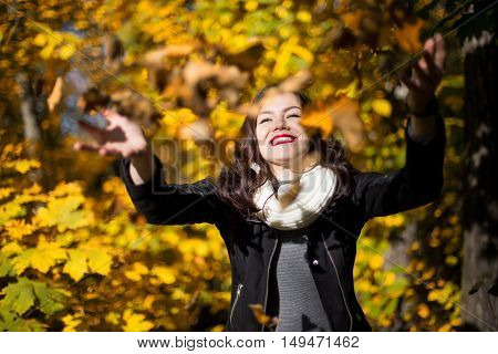 portrait of a girl close-up on a background of the autumn landscape and falling leaves