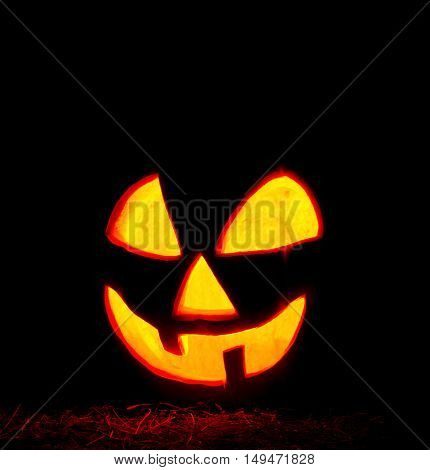 Scary Halloween pumpkin on black background. Glowing pumpkin with candle inside. Decorations for Halloween.