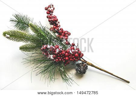 Pine twig with cones decorated with snow and ornaments for Christmas