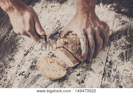 Baking and cooking concept background. Hands of baker cutting bread loaf with knife on rustic wooden table sprinkled with flour. Stained dirty hands of cook.
