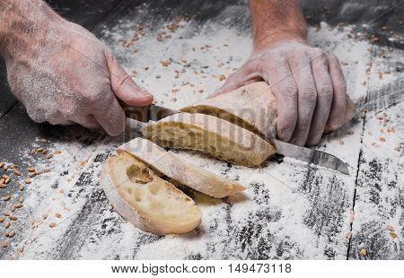 Baking and cooking concept background. Hands cutting bread loaf with knife on rustic wooden table sprinkled with flour. Stained dirty hands of baker.
