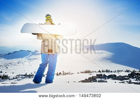 Girl snowboarder posing with snowboard on background of mountain