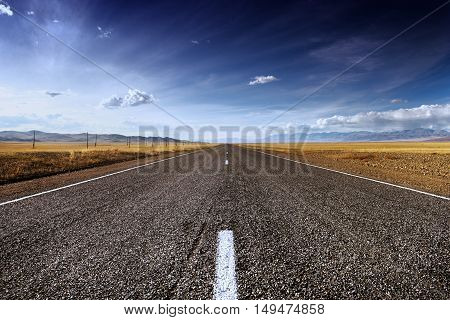 Straight long road in steppe on mountains backdrop