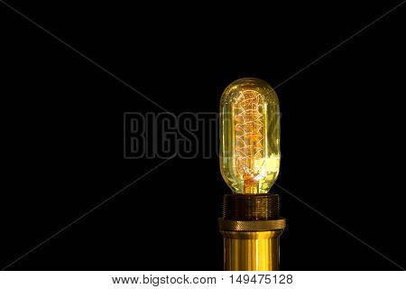 Tungsten light bulb glowing in isolated on black background