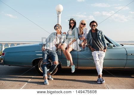 Portrait of happy young friends standing near cabriolet