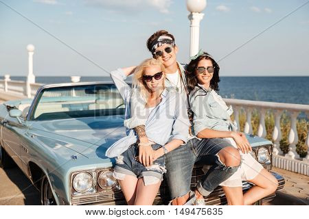 Smiling young man and two beautiful women standing together near vintage car