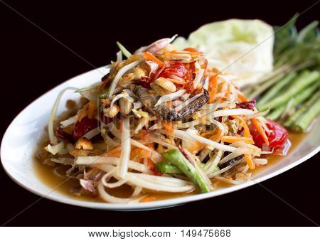 Papaya Salad Thai style (Som tum ) serve with fresh grees vegetable in black background