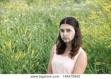 The girl with dark hair on a background of green grass