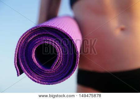 Sportive leisure woman with perfect body holding yoga mat with fitness bracelet on the left hand. Health life concept. Toned image.