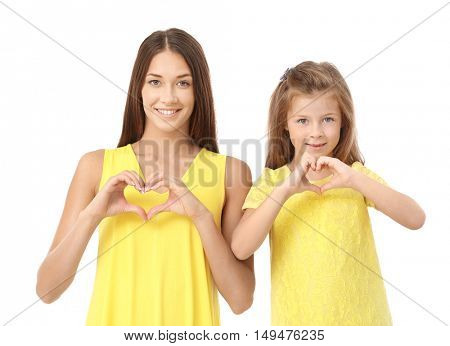 Cute girl and mother holding hands in heart shape on white background
