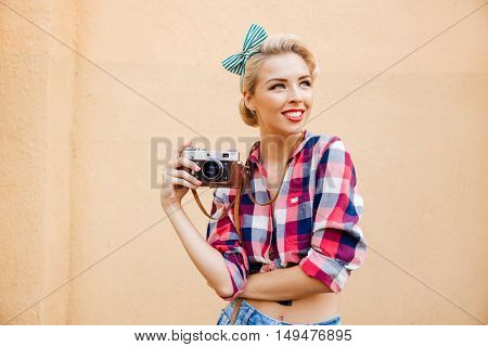 Beautiful cheerful pinup girl in yellow dress using vintage camera and taking pictures over pink background