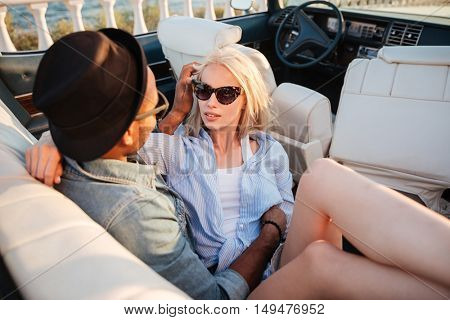 Sensual young couple sitting and embracing in cabriolet in summer