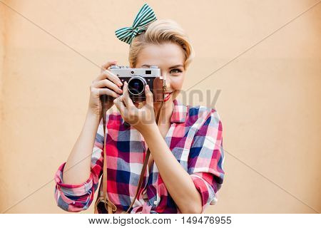 Smiling attractive young woman taking photos using old camera over pink background