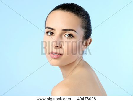 Attractive young woman with natural makeup on blue background