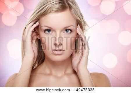 Portrait of beautiful female model on sparkling purple background