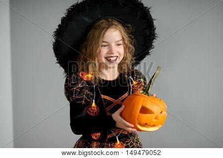 Portrait of the girl in a suit for Halloween. She represents the evel sorcerer. The girl is dressed in a black-orange dress a hat. In hands at her pumpkin - Halloween symbol. Children like Halloween.