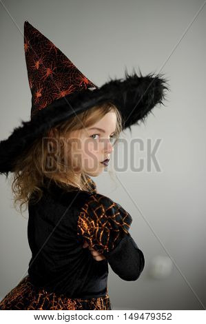 Preparation for Halloween. Cute girl 8-9 years shows the evil fairy. She is dressed in black and orange dress and a big hat. The girl tries to make an evil look. Children adore Halloween