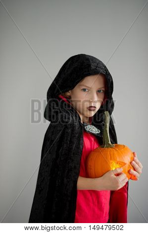 All Hallows Eve. Boy age dressed in a costume for Halloween. He represents the evil wizard. Boy is gowned in a black-red toga with a hood. He holds pumpkin with a candle inside - Halloween symbol.