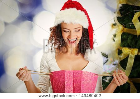 Beautiful happy woman with shopping bag and decorated Christmas tree on blurred lights background. Christmas holiday concept.