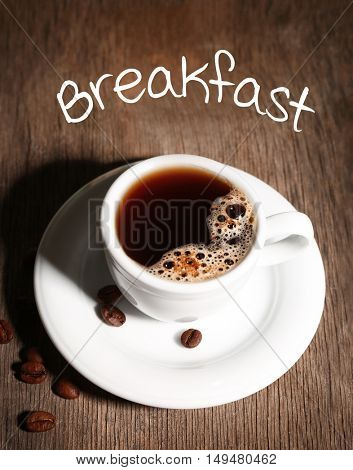 Word BREAKFAST and cup of aromatic coffee on wooden background, closeup