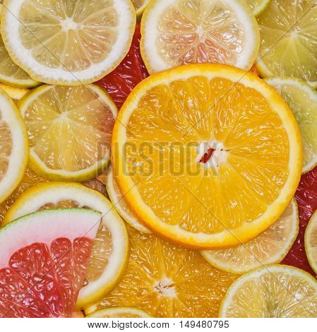 Natural background from slices of different citrus fruits. Healthy eating, diet, vitamins. Square