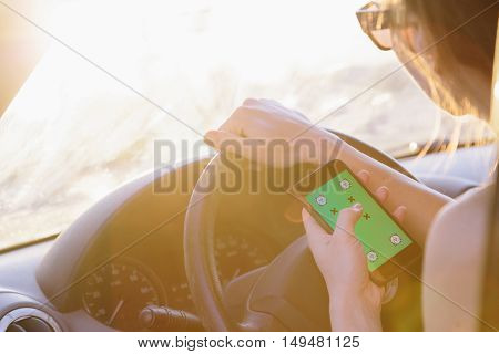 Young female driver using touch screen smartphone and gps navigation in a car. One hand on steering wheel.
