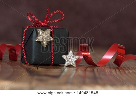 Still life with a gift for Christmas red bow and stars