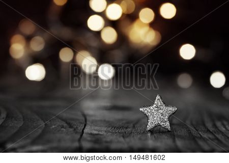 Silver christmas star in front of a festive background with golden lights