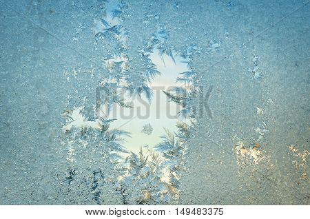 Frozen window at cold time. Iced surface. Frosty abstract background. Glass with the thawed hole