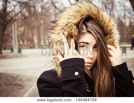 Portrait of a teenage girl with long beautiful hair outdoor wearing winter coat with the faux - fur hood on