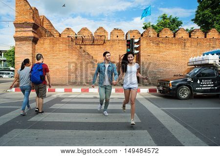 Chiang Mai Thailand - September 15 2016: Couple running across the crosswalk The Tha Pae gate in Chiang Mai Tha Pae Gate in Chiang Mai is a place where history is in the past: the inner city of Chiang Mai.
