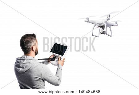 Man with remote control and flying drone with camera. Studio shot on white background, isolated.
