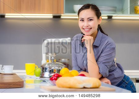Young beautiful happy asian woman in the kitchen