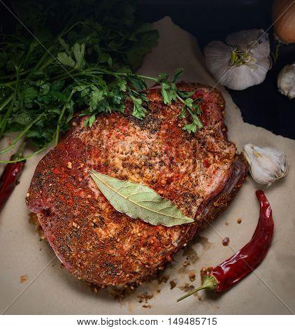 raw piece of pork, onion, pepper, garlic, parsley