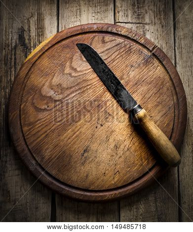 Vintage knife on a cutting board on a wooden background
