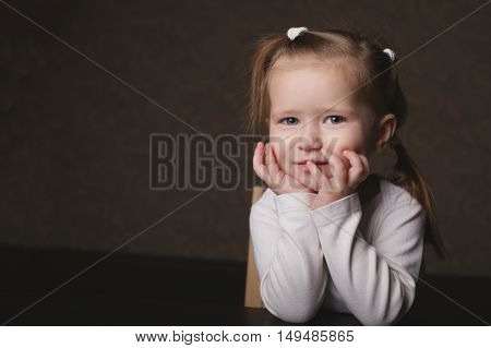 photo of little beautiful dreaming girl on grey background