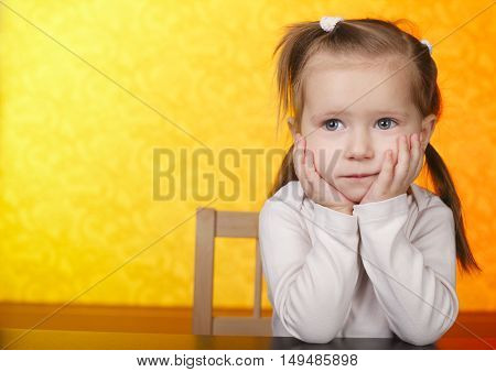 photo of little beautiful dreaming girl on yellow background