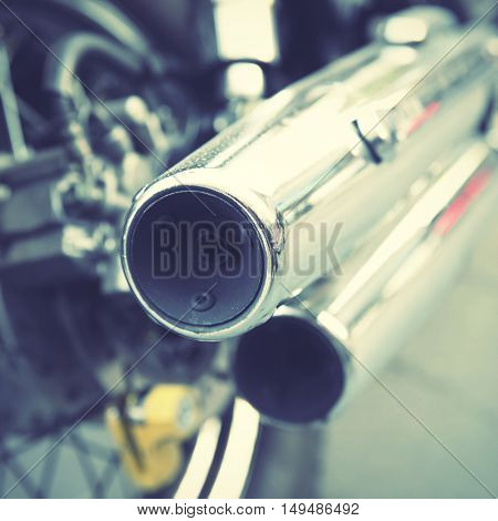 Chrome tailpipes of a motorbike. Shallow DOF!!! Retro style filtered image.