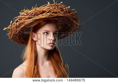 Closeup of beautiful woman in natural wreath of wicker, studio portait with copy space