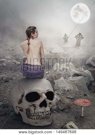 Beautiful woman sitting on the skull. Halloween mystical theme