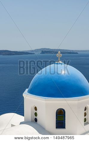 A view of a blue domed church from Oia overlooking the caldera on the greek isle of Santorini.